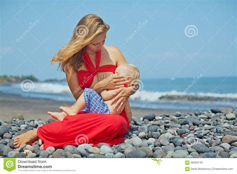 Mother With Baby Boy Sitting On The Sea Beach Stock Photo