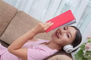 Ragazza Sdraiata Sul Divano Ascoltando Musica E Leggendo