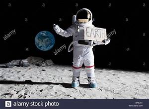 An astronaut on the moon with his thumb out, holding ...