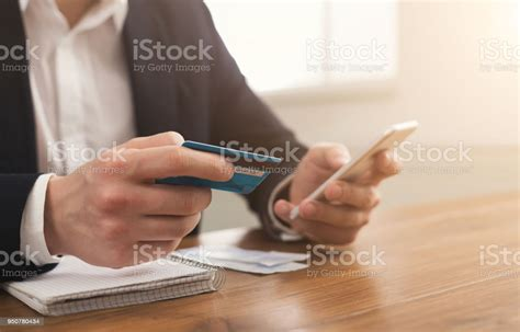Let's start with the premise that using a smartphone as a credit card could be dangerous. Mans Hands Holding A Credit Card And Using Smartphone Stock Photo - Download Image Now - iStock